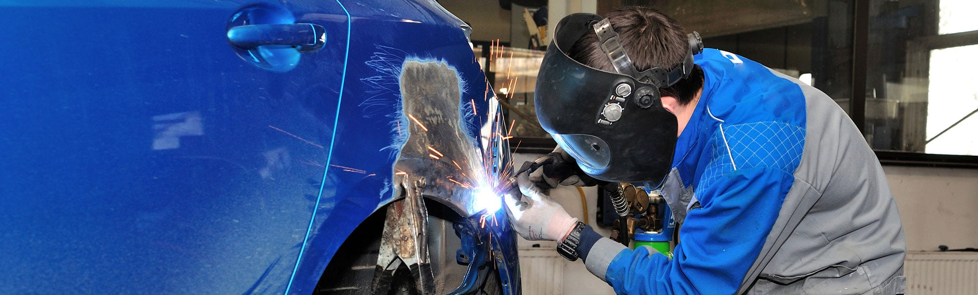 Body Pros welding part of a vehicles fender